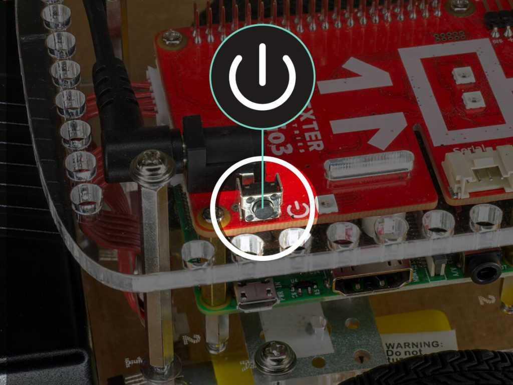The GoPiGo power button is located near the battery power cable board on the red electronic board.