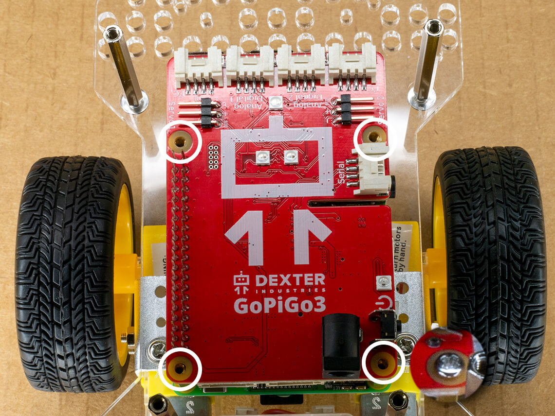 Use a small screw to secure the red GoPiGo electronic board using the four holes in the corners.